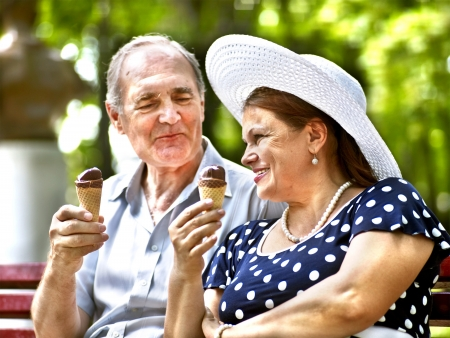 woman with ice cream: Happy old couple eating ice-cream outdoor. Stock Photo