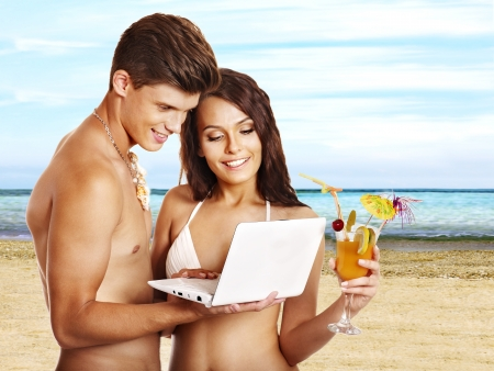 Couple with laptop at beach. Summer outdoor. photo