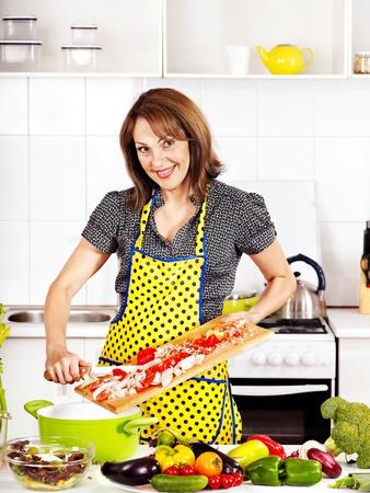 Happy woman preparing food at kitchen. photo