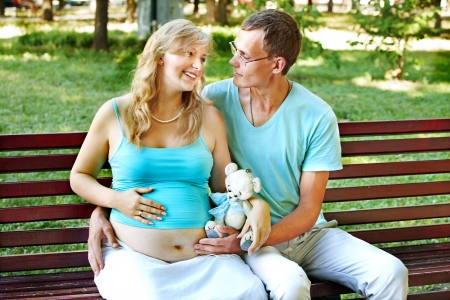 enceinte: Pregnant woman with man  holding teddy bear outdoor in park. Stock Photo