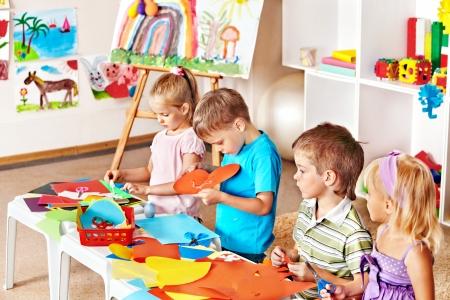 kinder: El ni?o hijo de cortar papel tijeras en preescolar. Foto de archivo