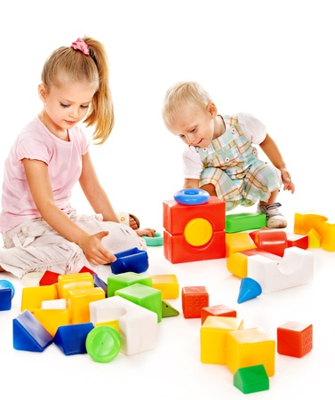 Happy children playing building blocks. Isolated. photo