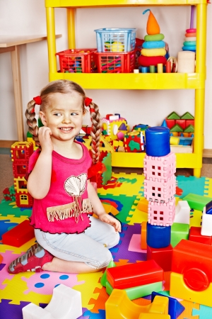nurser: Child with puzzle, block and construction set in play room. Preschool.