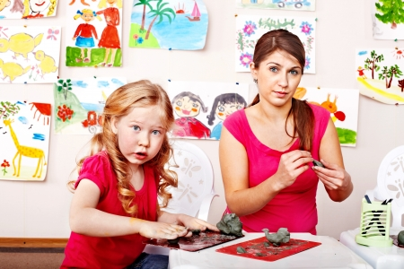 nurser: Teacher and little girl  playing with  clay. Stock Photo