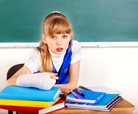 broken arm: Child with broken arm in classroom. Stock Photo