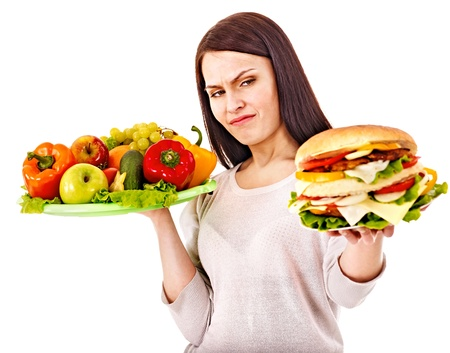 fatty food: Woman choosing between healthy and unhealthy eating.