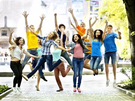 personas saltando: Grupo de estudiantes con port?til al aire libre de verano. Foto de archivo