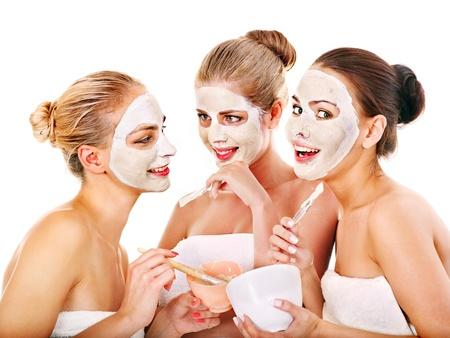 ansikts: Ung kvinna att få ansiktsmask och skvaller. Isolerade.
