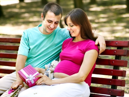 Pregnant woman, holding shopping bag with man outdoor. photo