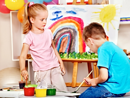 paintings: Child painting at easel in school. Education.