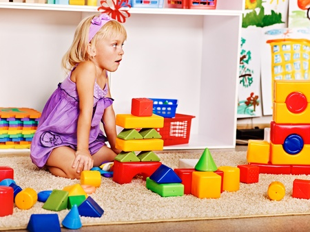 Little girl in kindergarten stacking block. photo