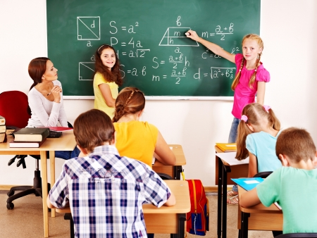 back to school: School child with teacher in classroom. Stock Photo