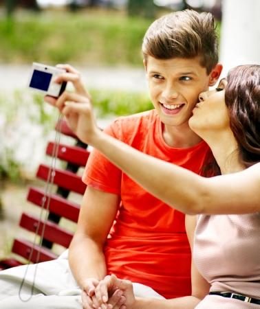 enamorados besandose: Pares con la cámara toma imágenes en el banco. Al aire libre.