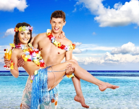 Couple with cocktail at Hawaii wreath beach. Guy holding girl in his arms