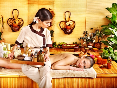 Young woman getting massage in bamboo spa. Stock Photo - 21572633