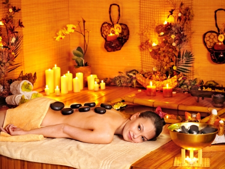 massage oil: Woman getting stone therapy massage in bamboo spa.