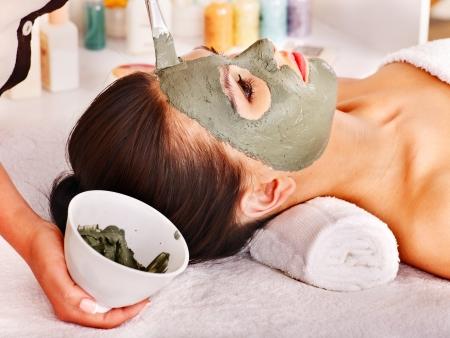 facial treatment: Woman with clay facial mask in beauty spa. Stock Photo