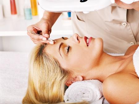tweezing eyebrow: Woman getting tweezing eyebrow. Stock Photo