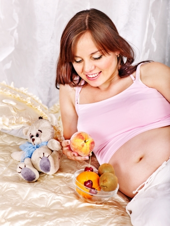 Pregnant woman holding teddy bear at bedroom. photo