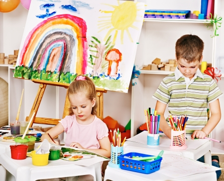 kids club: Child painting at easel in school. Education.