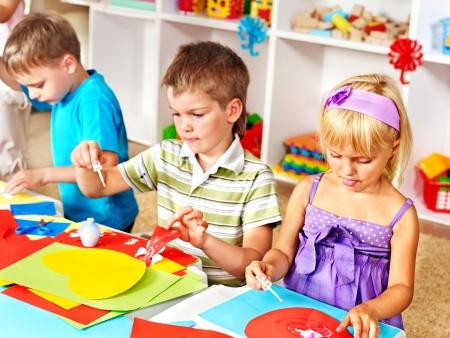 niños jugando en la escuela: El ni?ijo de cortar papel tijeras en preescolar. Foto de archivo