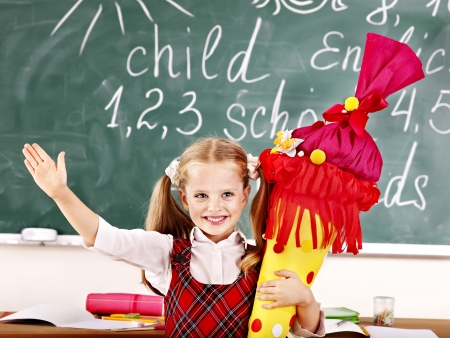 Little girl in classroom holding  school cone. photo