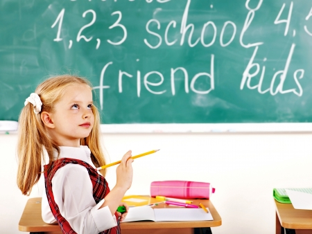 first day of school: Child with backpack writting text on blackboard. Stock Photo