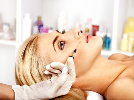 botox: Doctor woman giving botox injections. Isolated.