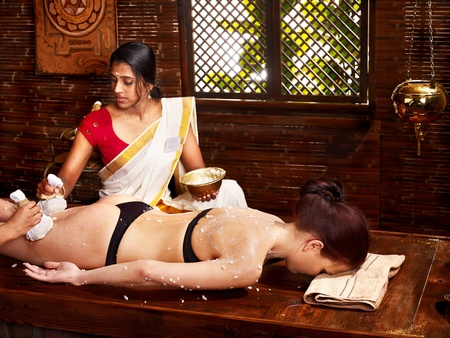 Woman having Ayurveda massage with pouch of rice. Stock Photo - 21559223