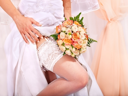 Garter at leg of bride and flower bouquet. photo