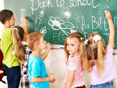 niños escribiendo: Niños que escriben en la pizarra en la escuela. Foto de archivo