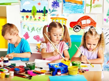 niños pintando: Ni?o pintura en caballete en la escuela. Maestro ayuda.
