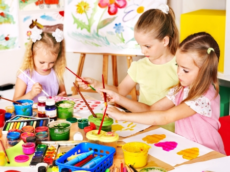 kids class: Child painting at easel in school. Teacher help.