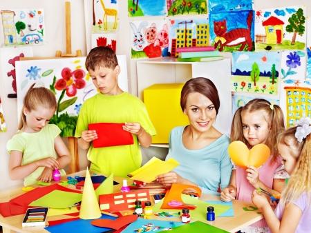 playschool: Children  cutting out scissors paper in preschool.
