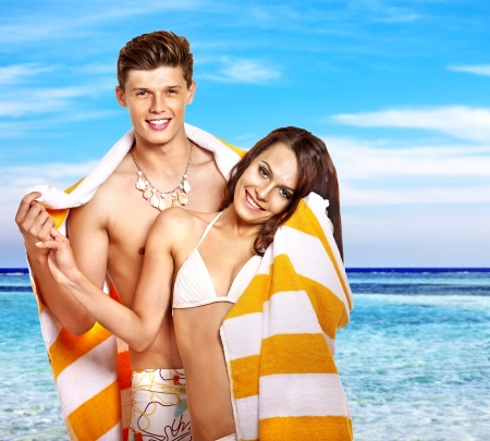 Couple with towel at  beach. Summer outdoor. photo