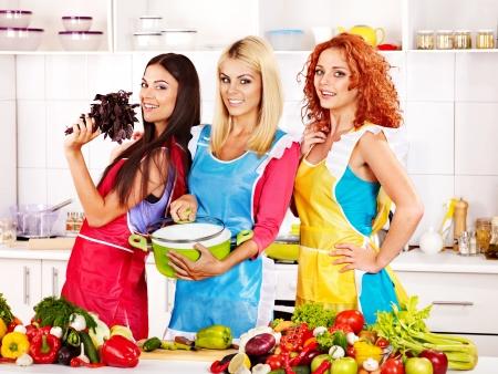 comidas saludables: Mujeres felices del grupo de preparar la comida en la cocina.