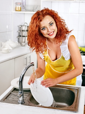 lavar trastes: Mujer feliz lavando platos en la cocina. Foto de archivo