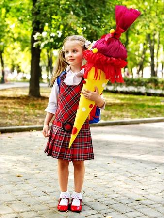 schoolgirl uniform: Child holding gift school cone. Outdoor. Stock Photo