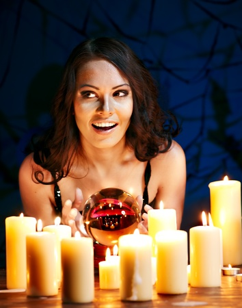 scrying: Woman holding scrying ball and candle.