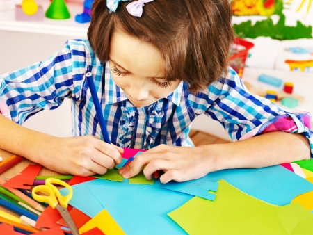 child drawing: Little girl with  scissor  at school. Education. Stock Photo