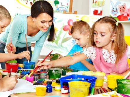 preschool education: Happy children  with teacher painting. Stock Photo
