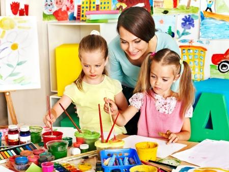 preschool classroom: Happy children  with teacher painting. Stock Photo