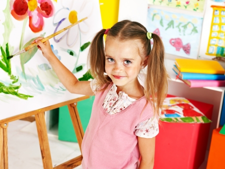 Child painting at easel in art class. photo