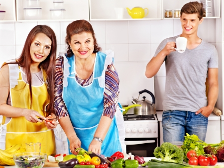 Mature woman with family preparing  dinner at kitchen. photo