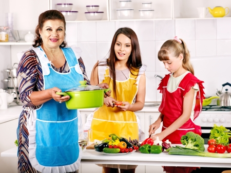 preparing food: Family with grandmother and child cooking at kitchen.