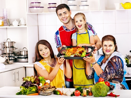 Happy family with grandmother at kitchen. Cooking chicken. Stock Photo - 21735240