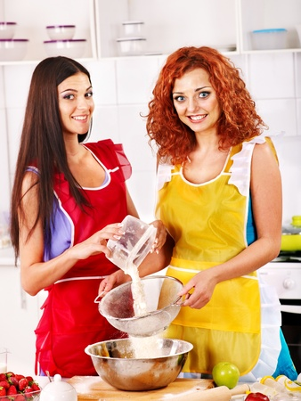 Couple  women  cookies  baking in oven. photo