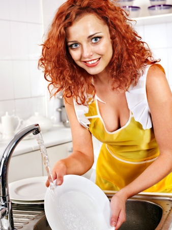 Happy woman washing dishes at kitchen.