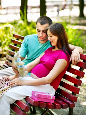 enceinte: Pregnant woman, holding flower with man  outdoor in park.
