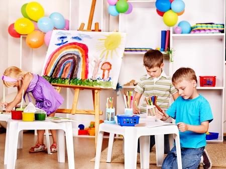 グループの子が学校でイーゼルの絵画します。 写真素材